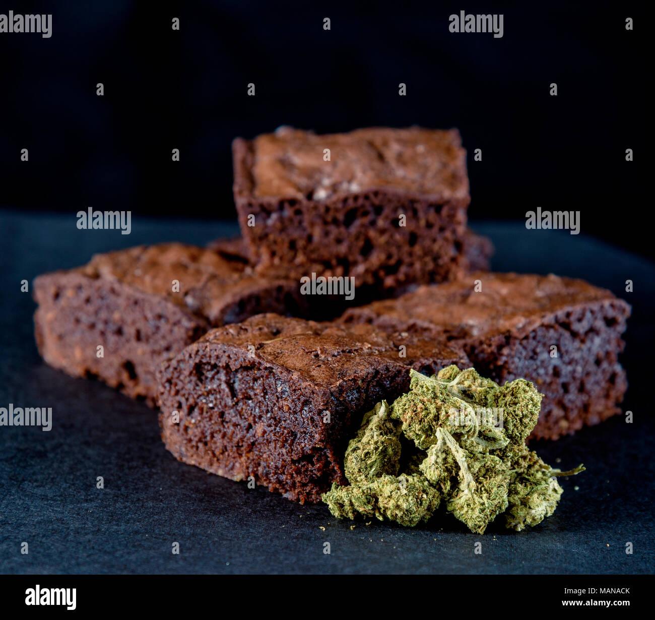 A stack of marijuana edible brownies next to a small pile of medical marijuana nugs. Black background - Stock Image