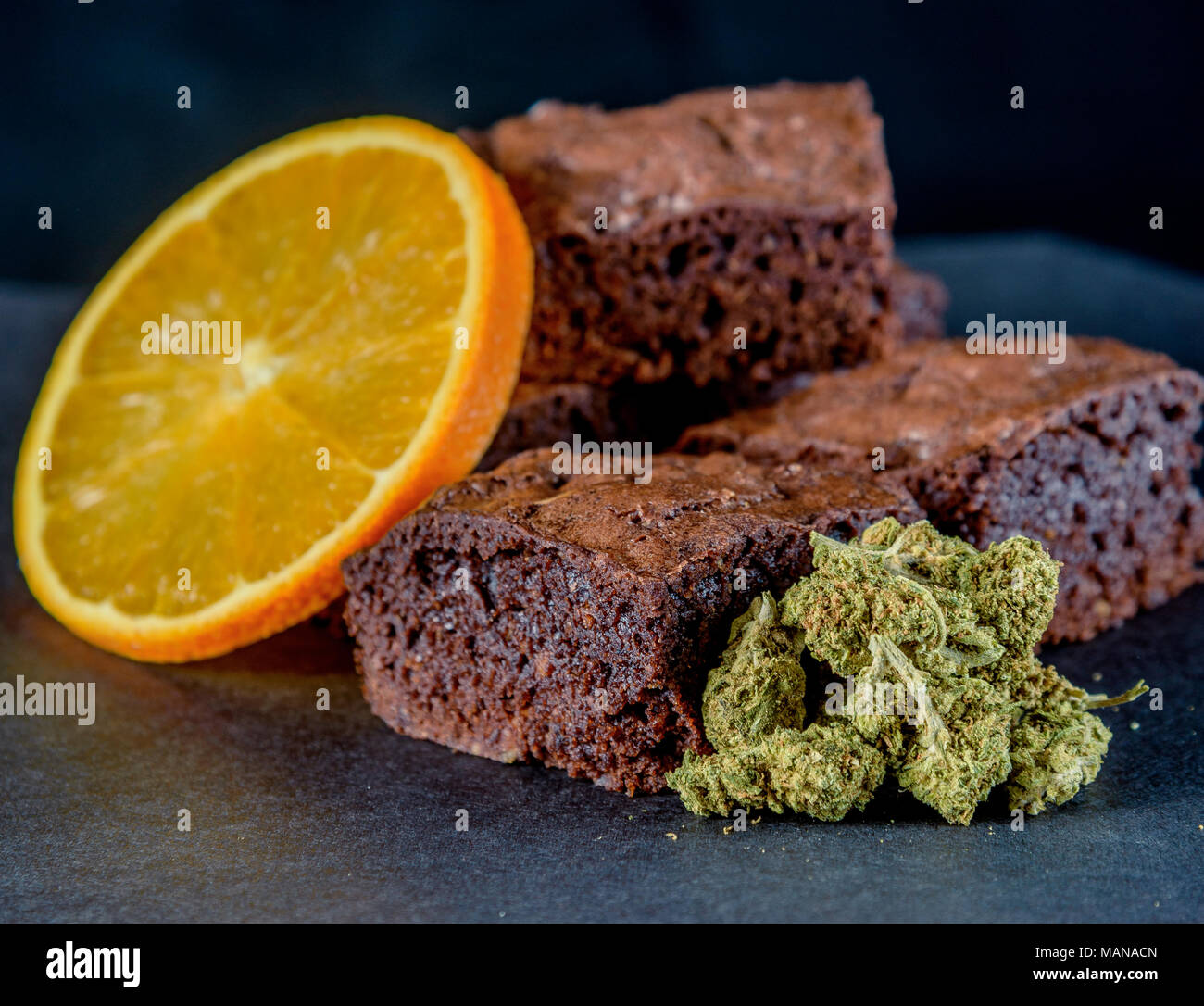 A stack of marijuana edible brownies next to a small pile of medical marijuana nugs and an orange slice. Black background - Stock Image