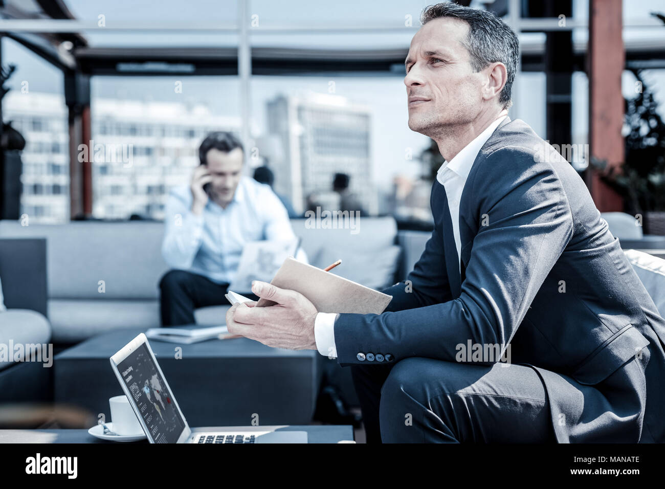 Pleasant thoughtful businessman thinking about his work - Stock Image