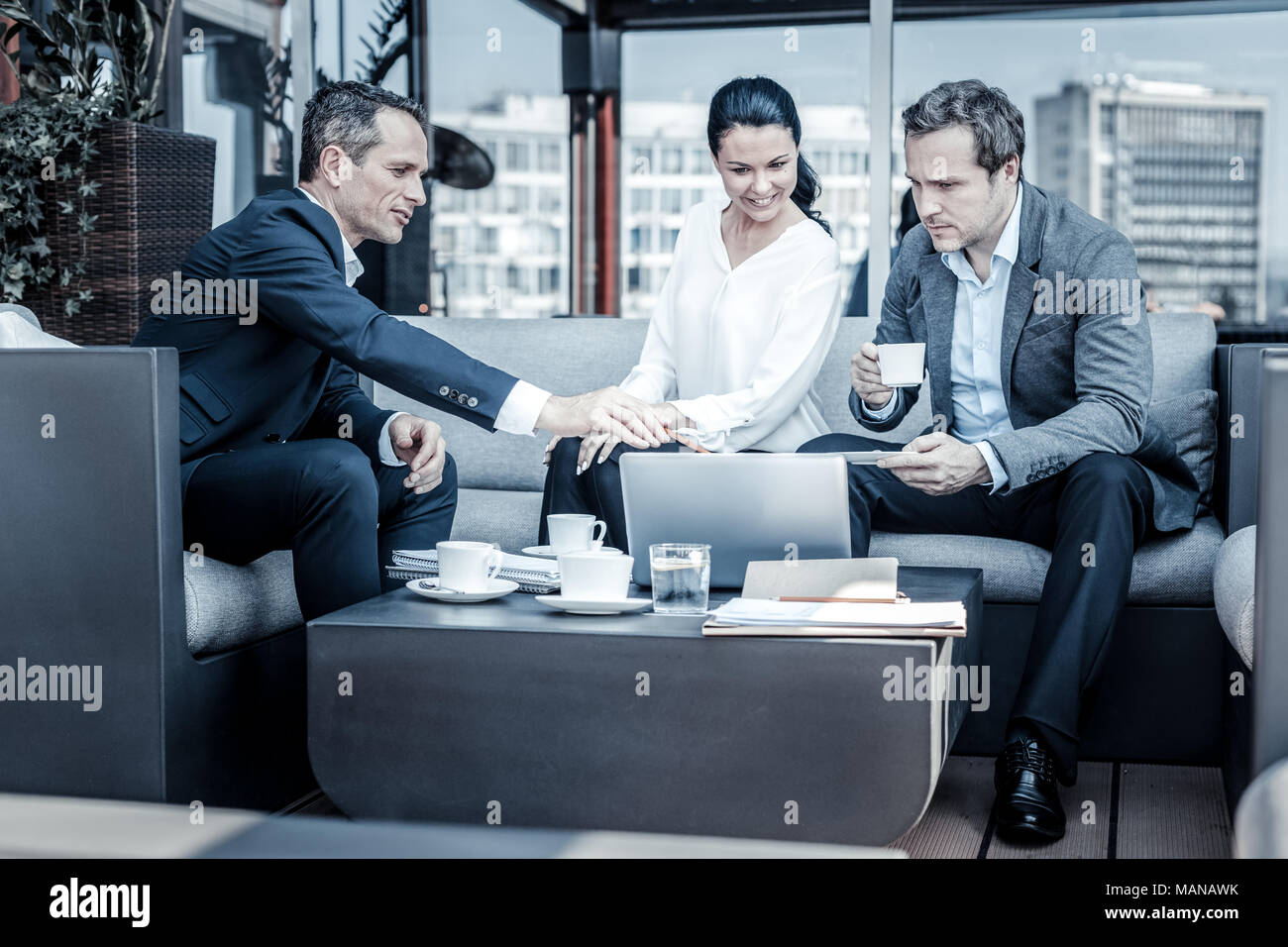 Pleasant nice businesspeople discussing their project - Stock Image
