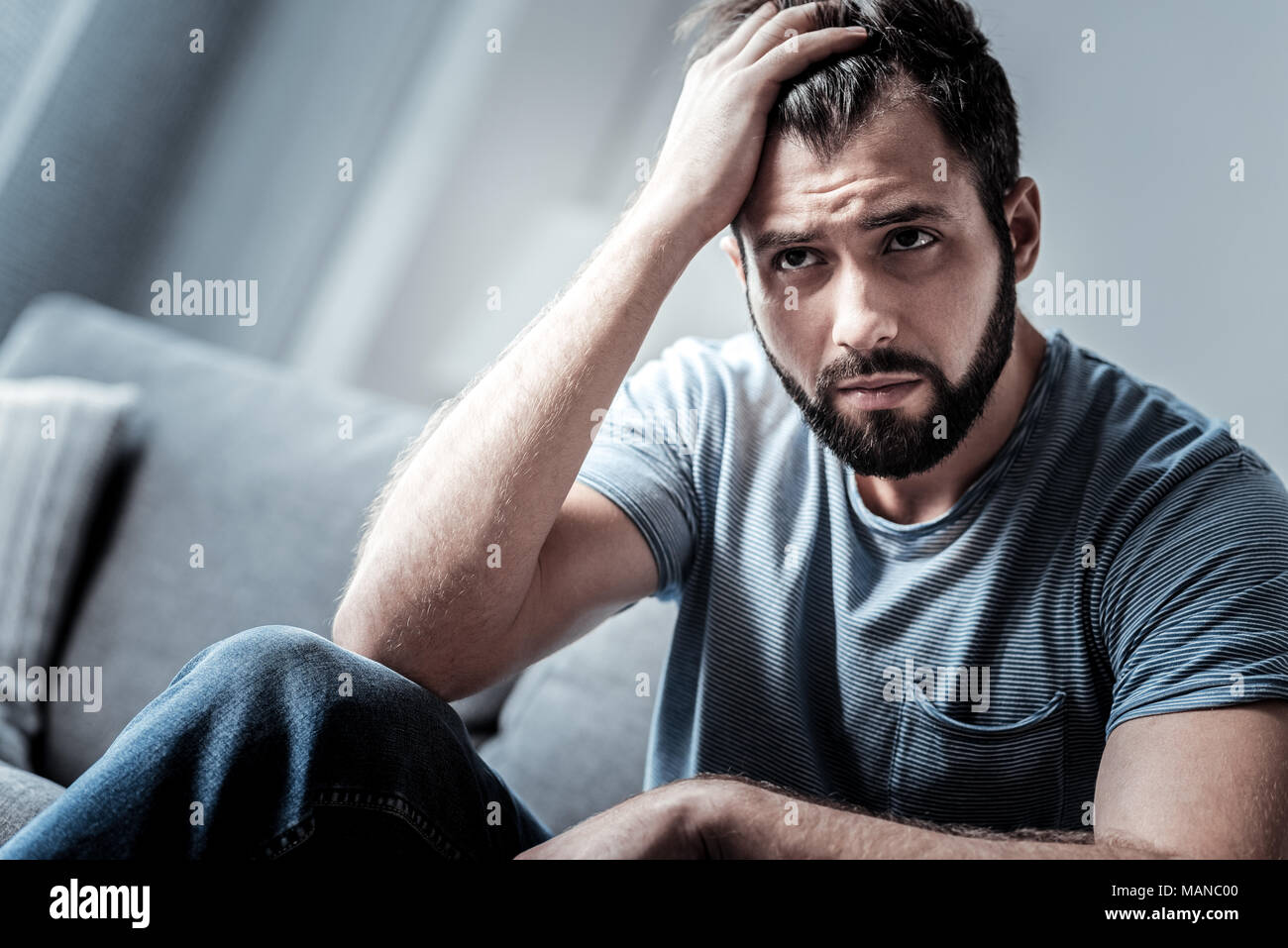 Sad young man being in a difficult situation - Stock Image