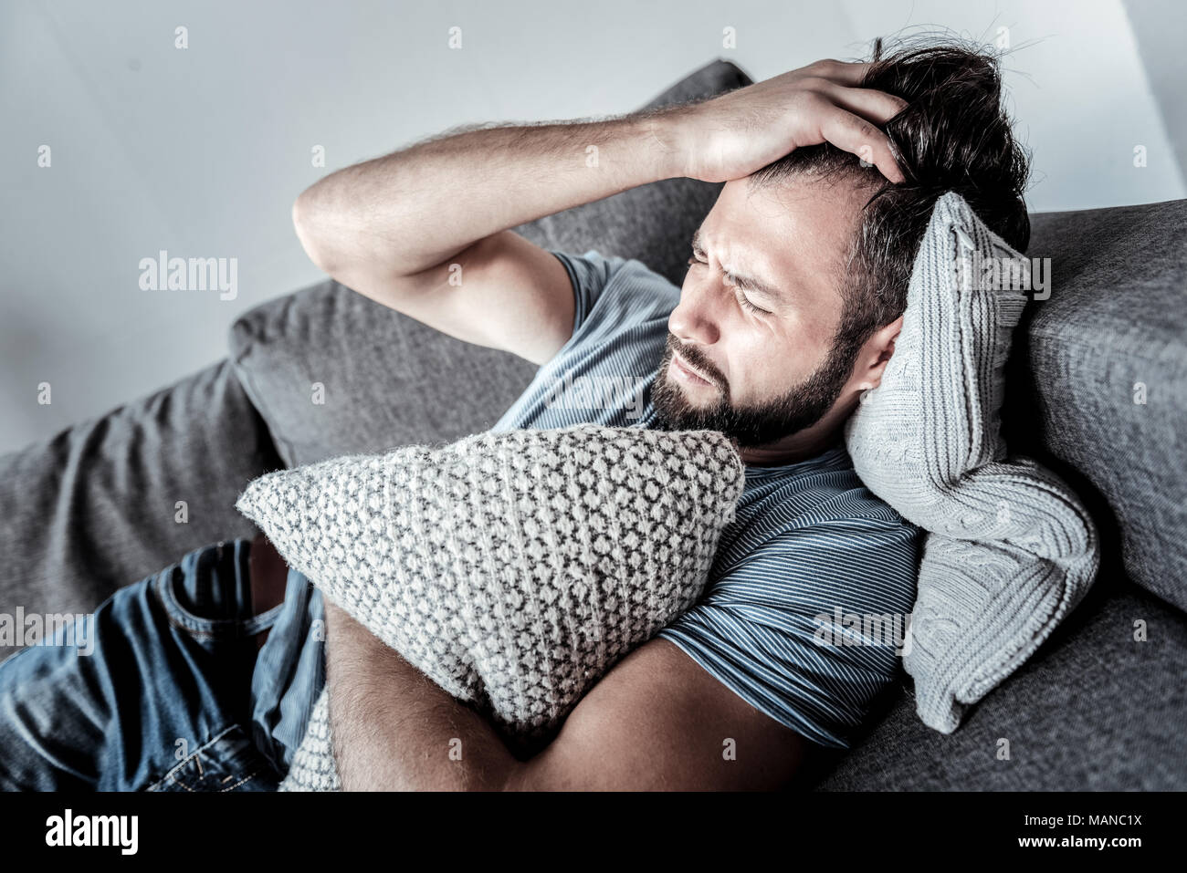 Unhappy young man suffering from depression - Stock Image