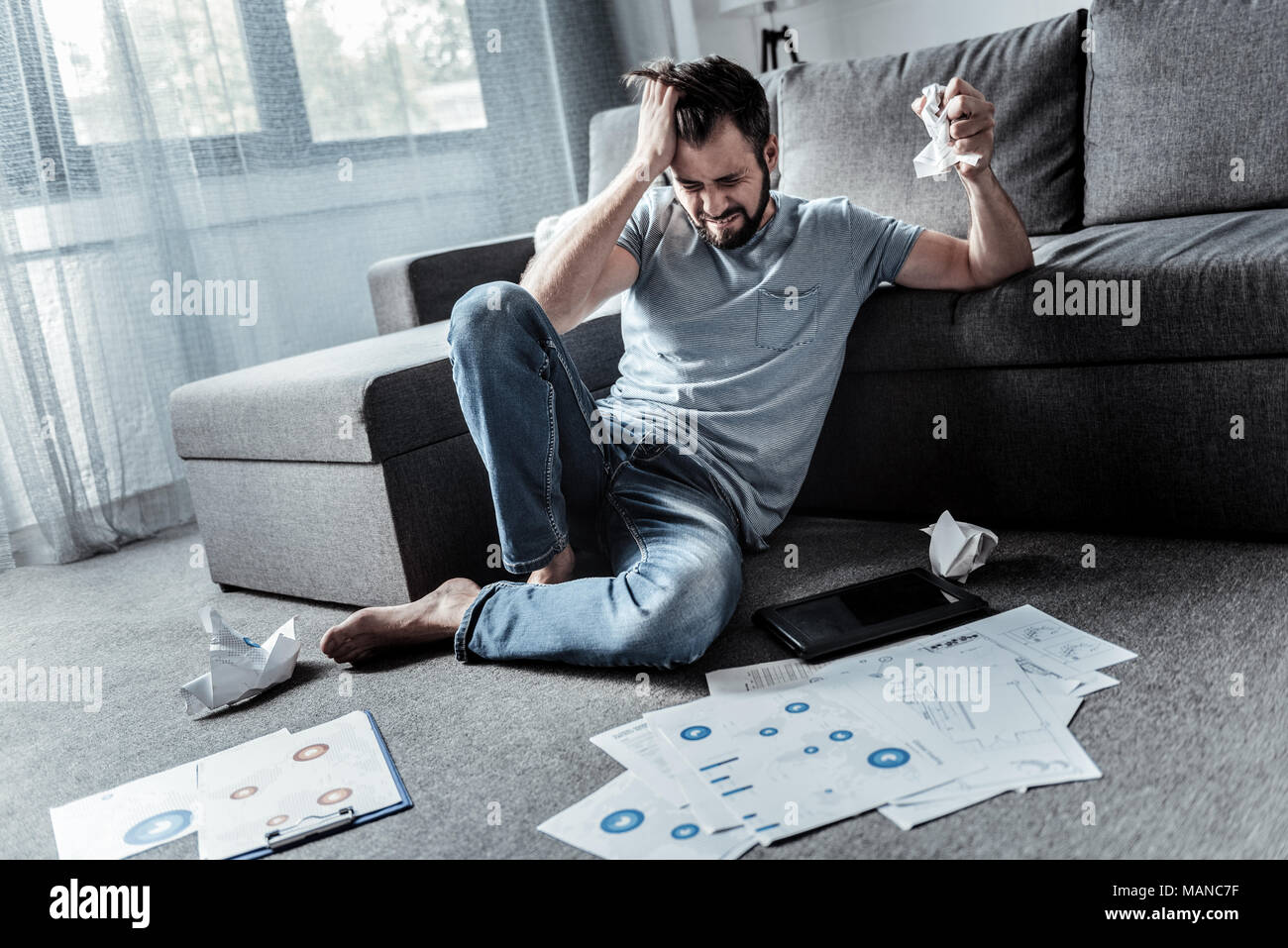 Depressed angry man not coping with his work - Stock Image