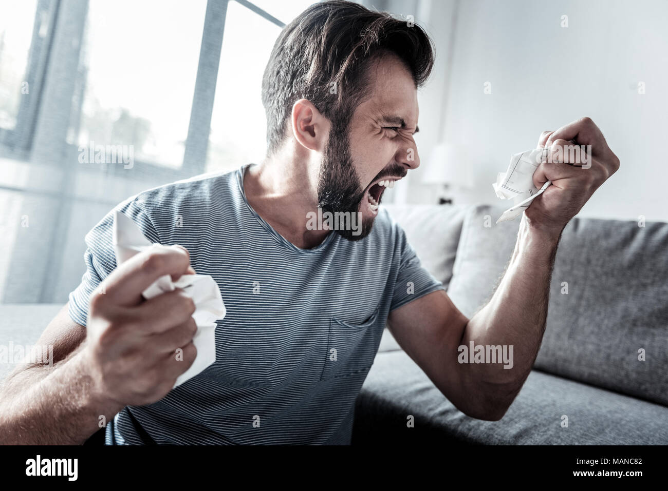 Angry unhappy man expressing his emotions - Stock Image