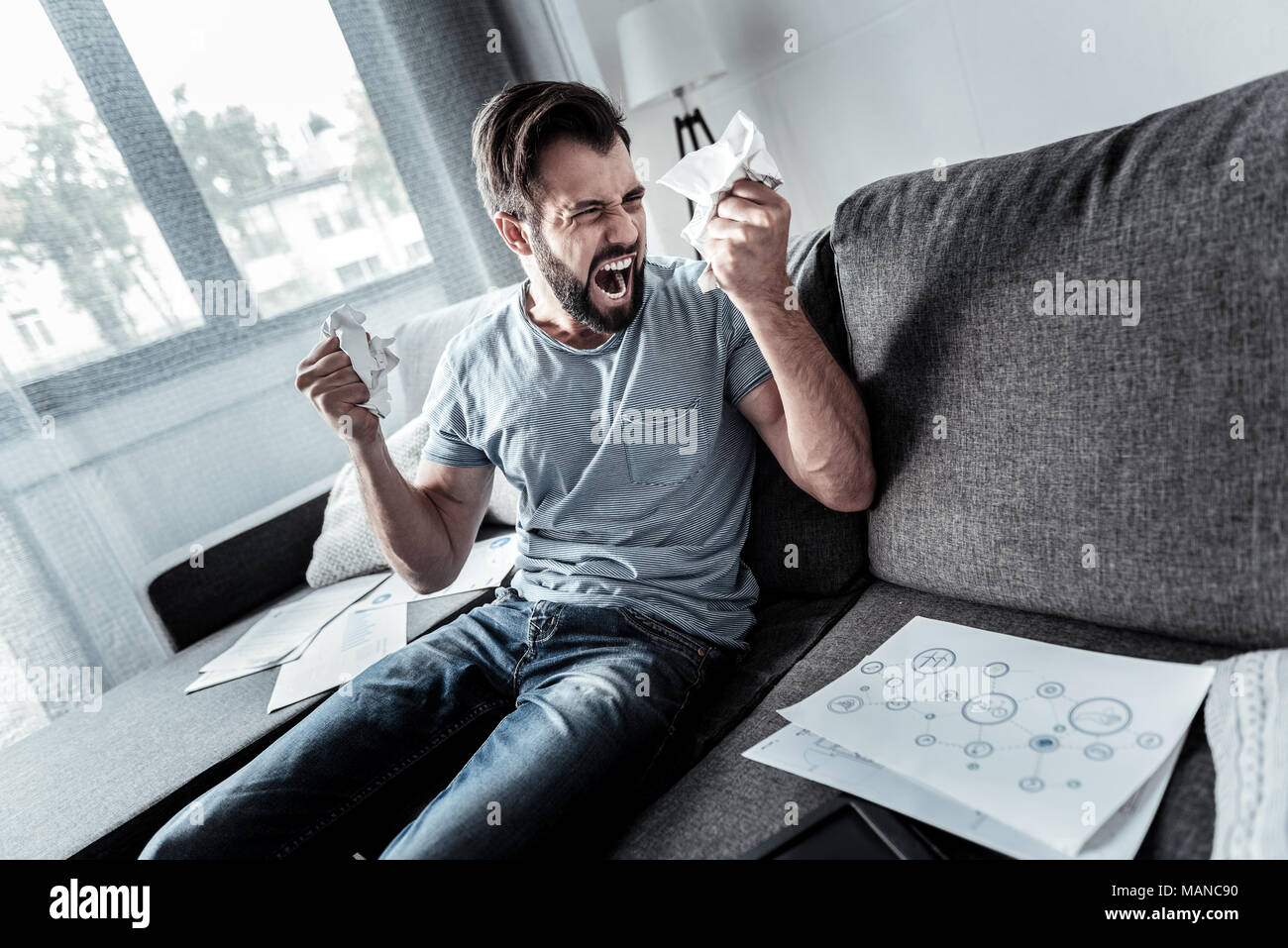Angry emotional man crumpling paper - Stock Image