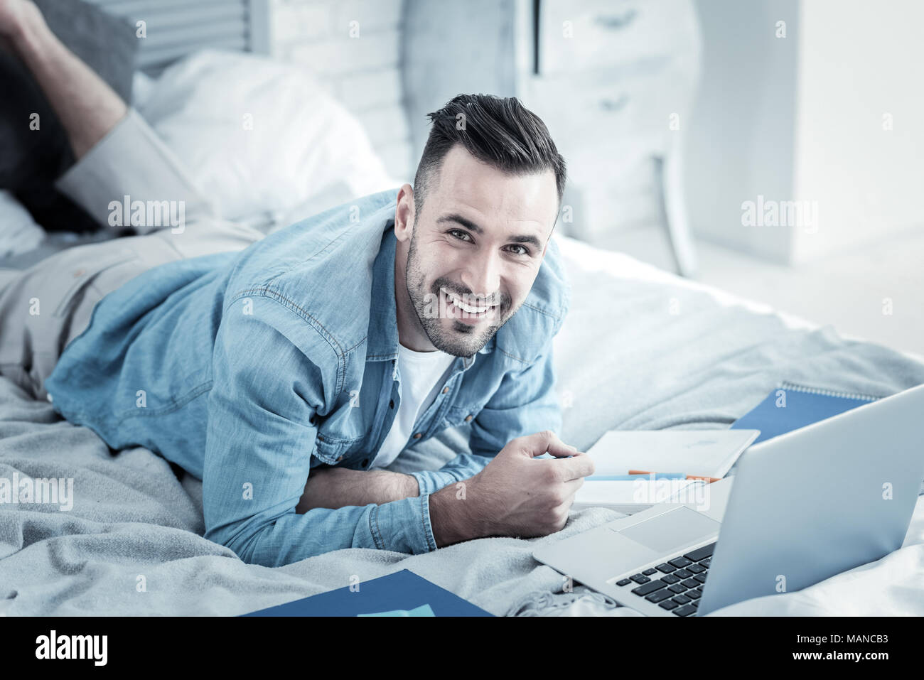 Cheerful nice man studying from home - Stock Image