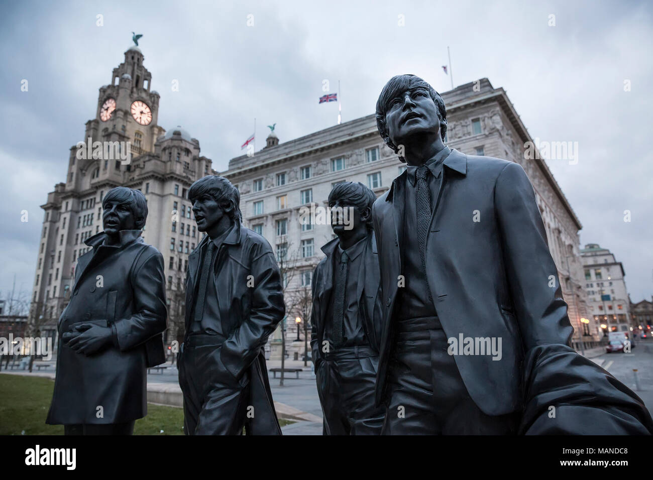 LIVERPOOL, UK - March 18, 2018 : Close up of the Beatles statues at the pier head in Liverpool with the Royal Liver Building in the background. - Stock Image