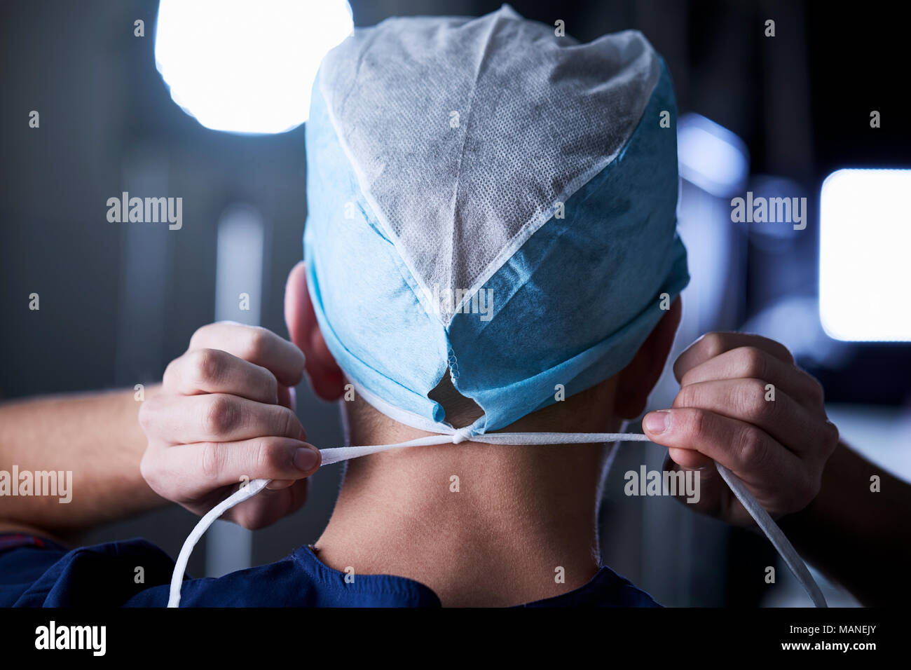 Surgeon tying surgical cap in preparation, back view - Stock Image