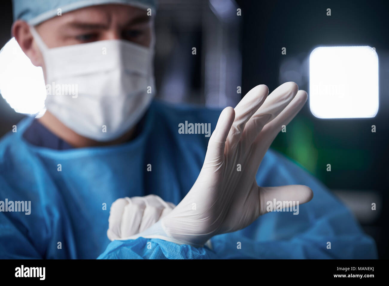 Male surgeon putting on latex gloves in preparation - Stock Image