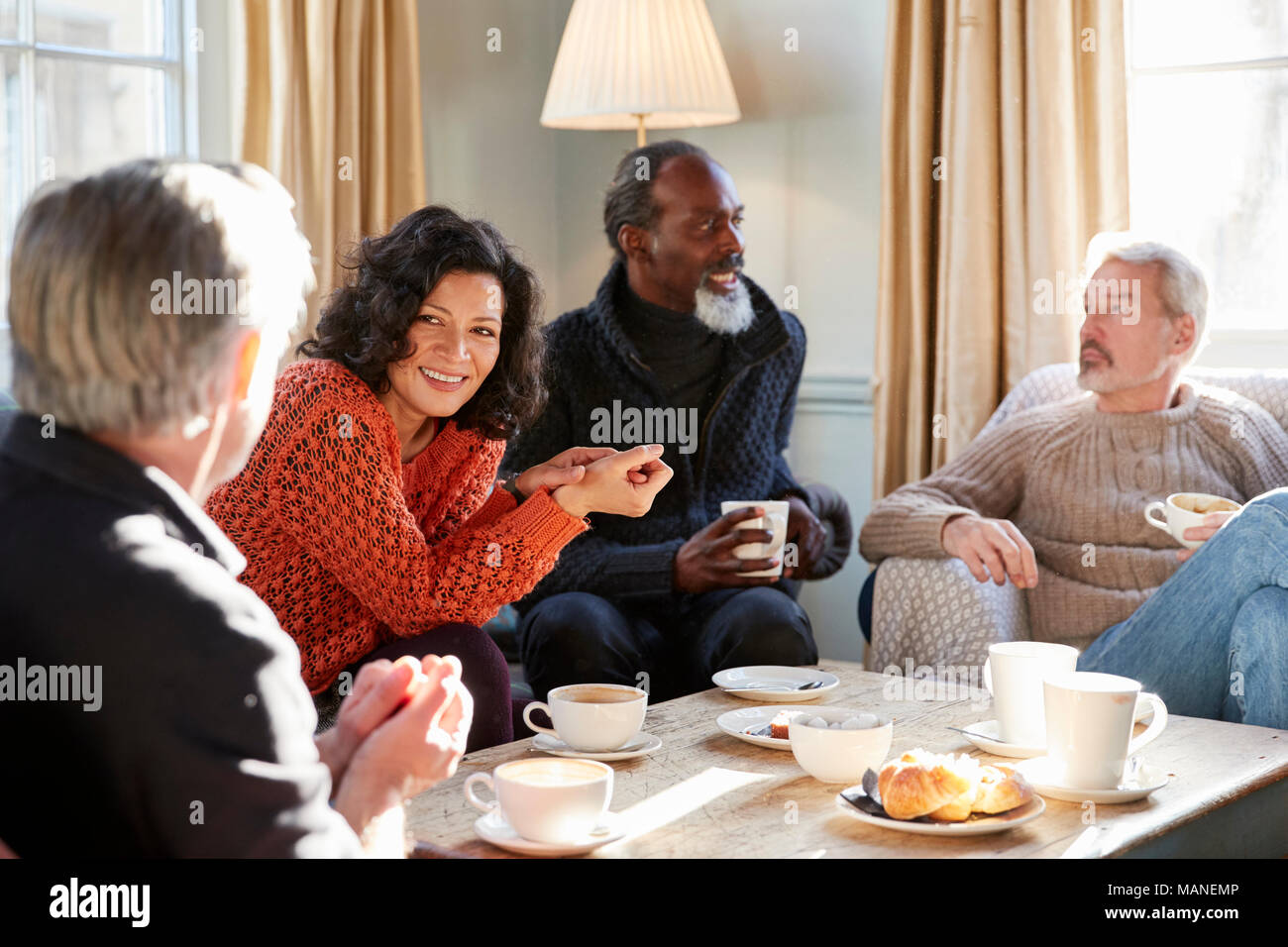 Group Of Middle Aged Friends Meeting Around Table In Coffee Shop - Stock Image