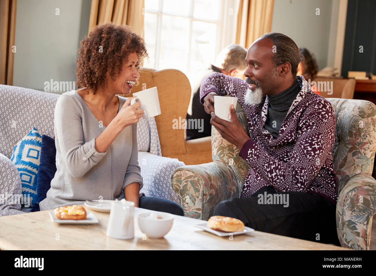Middle Aged Couple Sitting Around Table In Coffee Shop - Stock Image