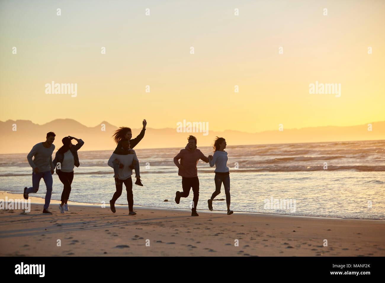 Silhouette Of Friends Having Fun Running Along Winter Beach - Stock Image