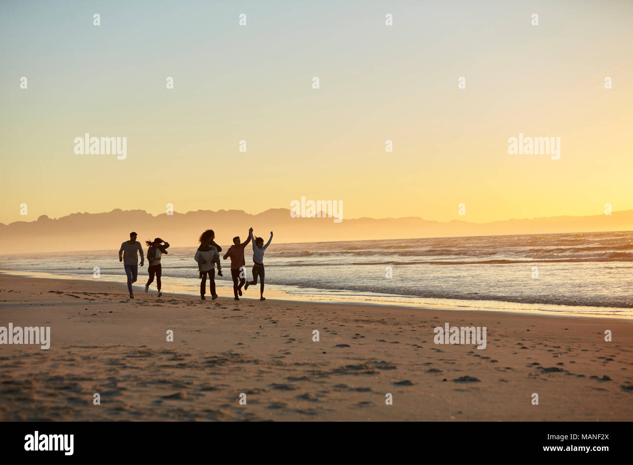 Silhouette Of Friends Having Fun Running Along Winter Beach - Stock Image