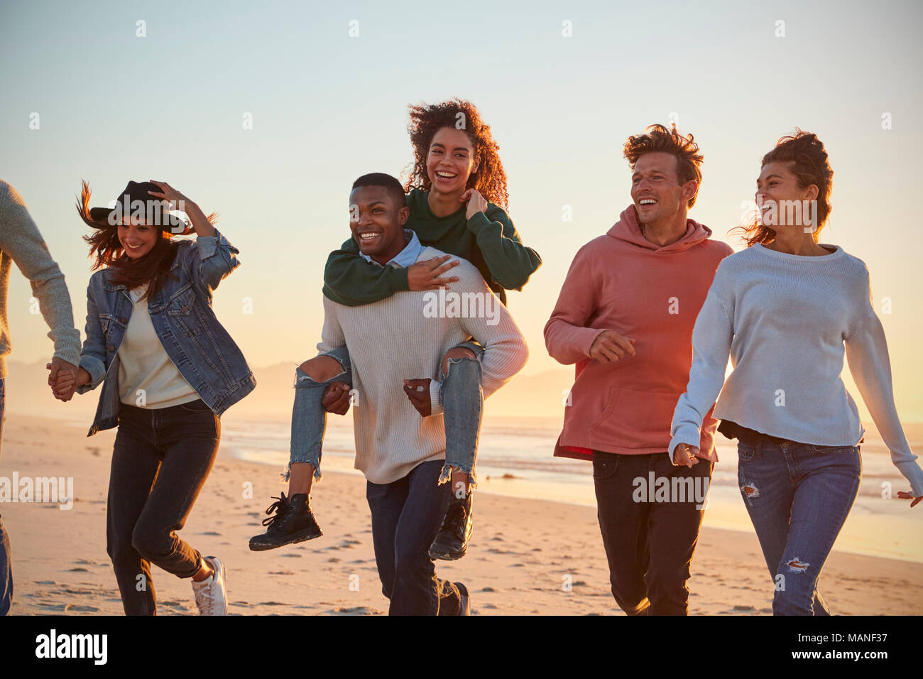 Group Of Friends Having Fun Running Along Winter Beach Together - Stock Image
