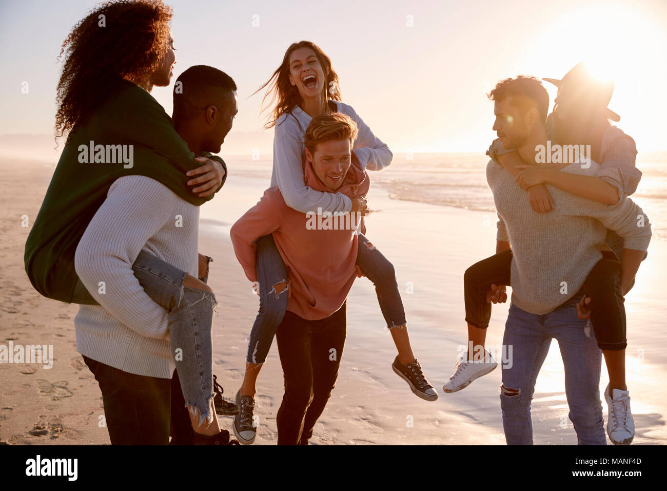 Group Of Friends Having Piggyback Race On Winter Beach Together - Stock Image