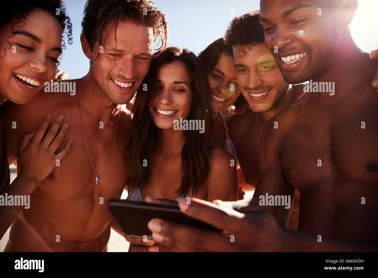 Friends On Beach Vacation Looking At Photo On Mobile Phone - Stock Image