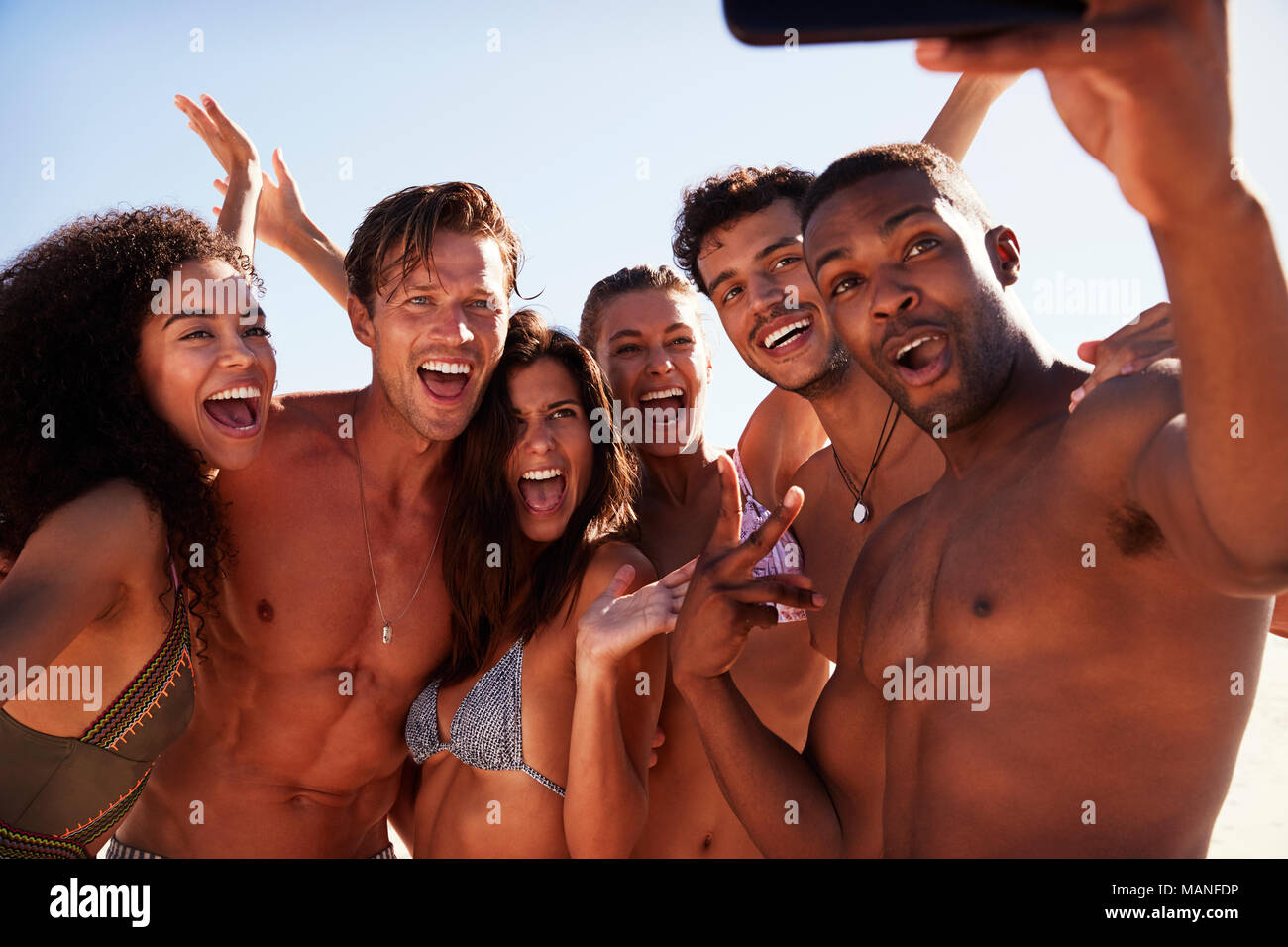 Group Of Friends Posing For Selfie Together On Beach Vacation - Stock Image