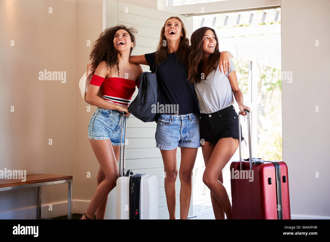 Group Of Female Friends Arriving At Summer Vacation Rental - Stock Image