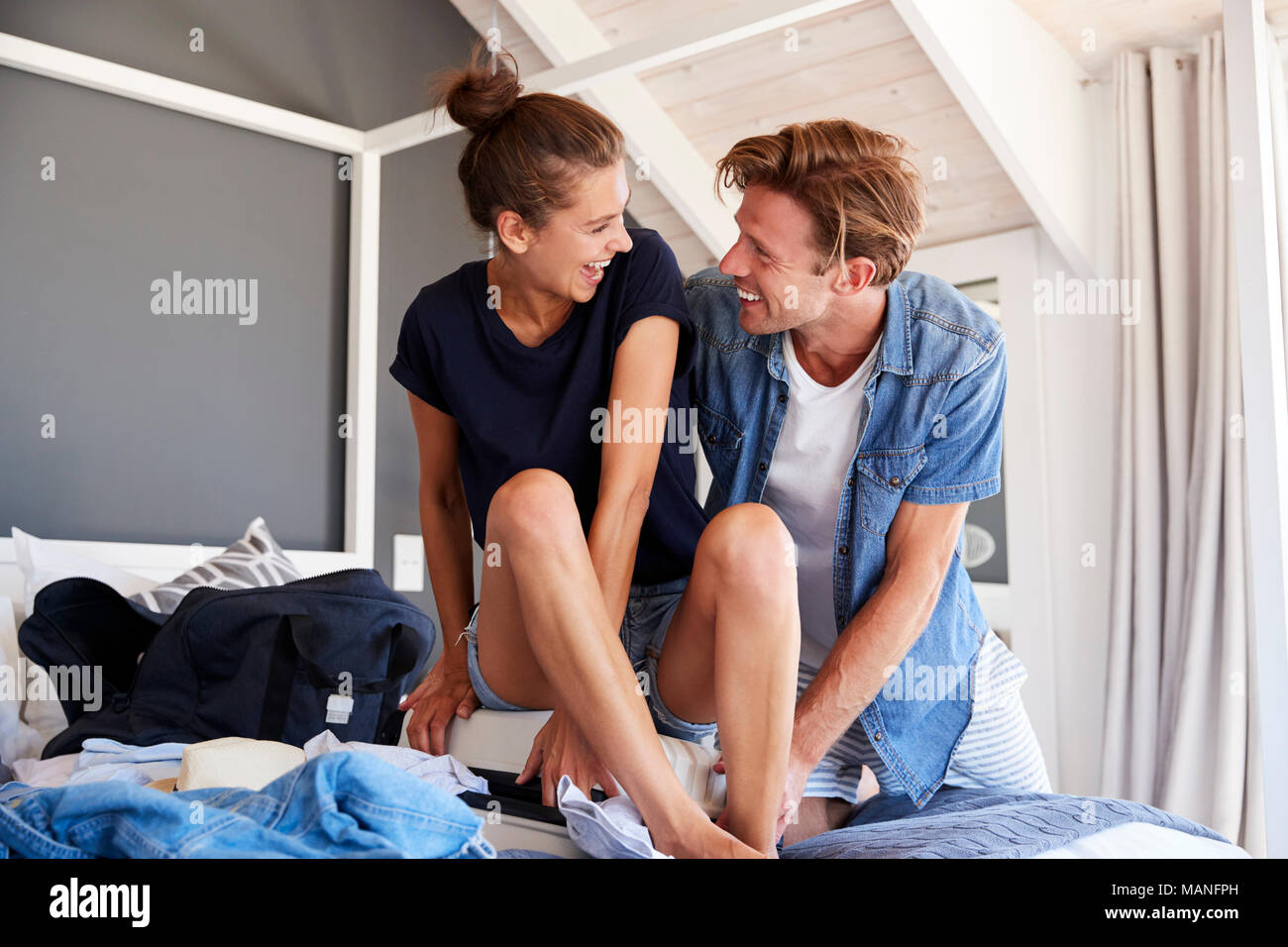 Couple Trying To Close Full Holiday Suitcase In Bedroom Stock Photo