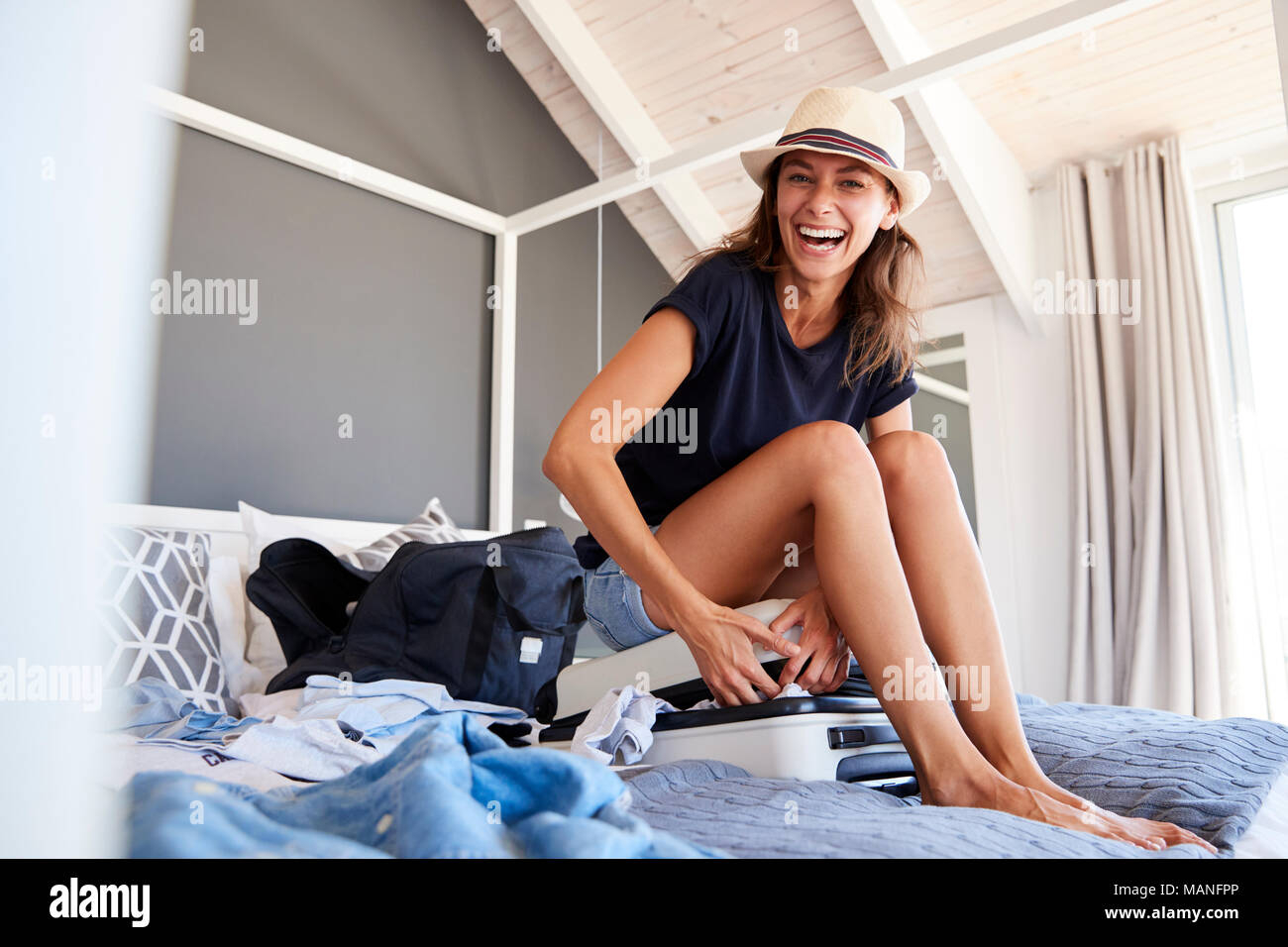 Portrait Of Woman Trying To Close Full Holiday Suitcase - Stock Image