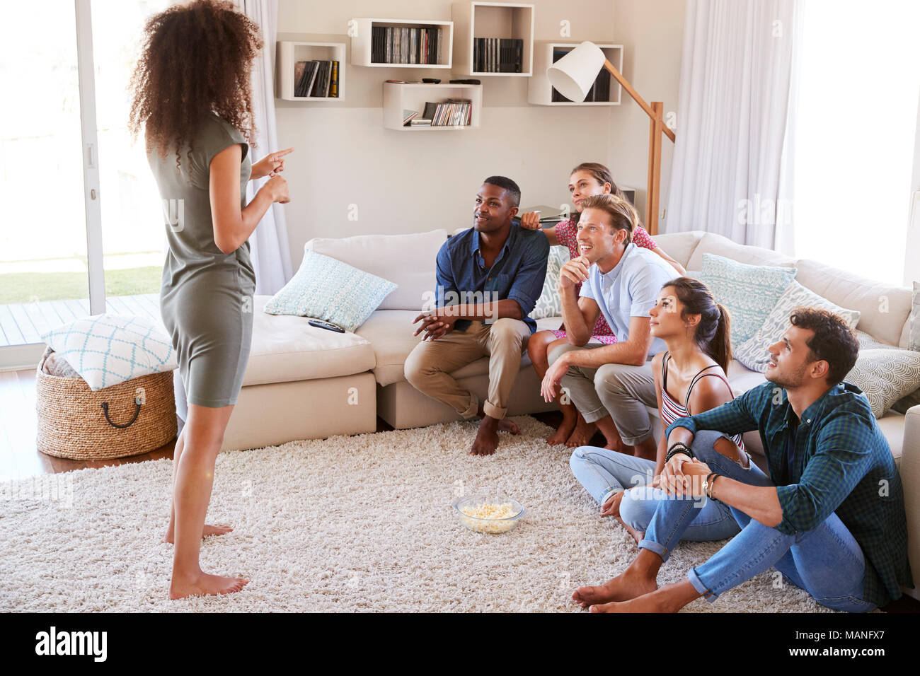 Group Of Friends At Home Having Fun Playing Charades Together - Stock Image