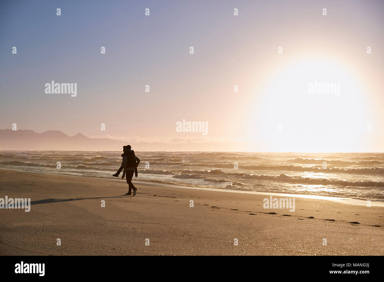 Silhouette Of Father Giving Son Piggyback On Winter Beach - Stock Image