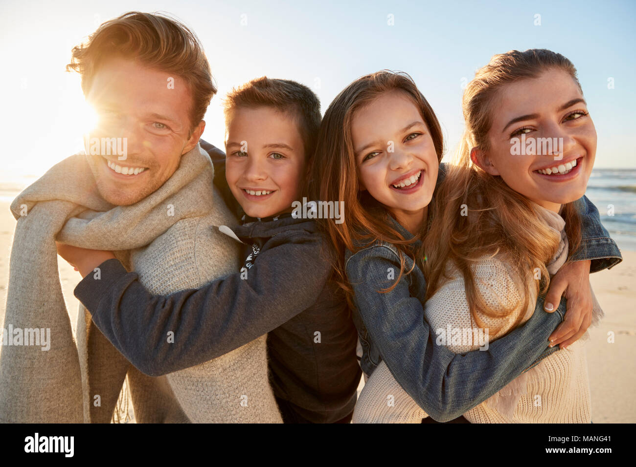 Parents Giving Children Piggyback Rides On Winter Beach - Stock Image