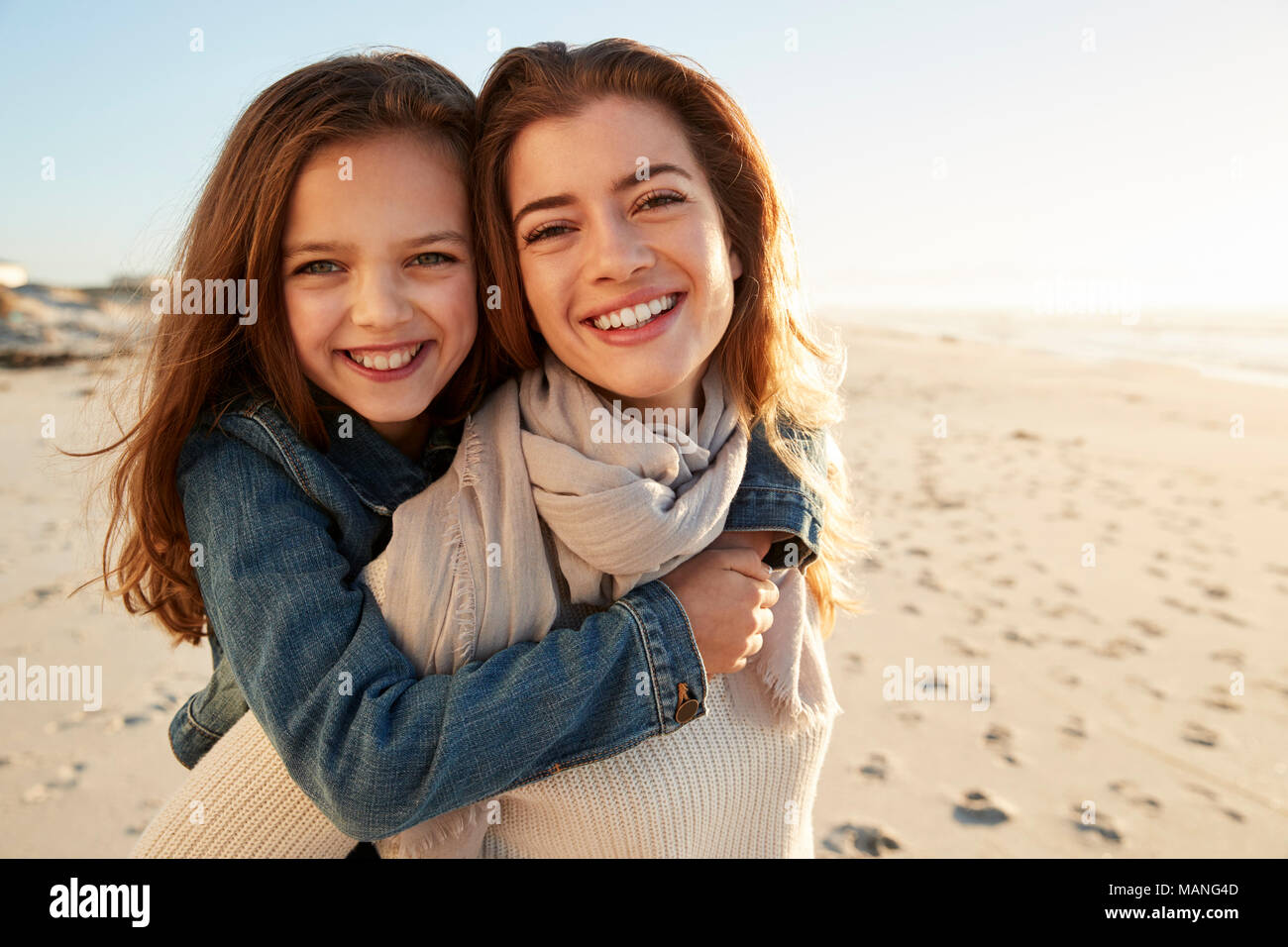 Portrait Of Mother Giving Son Piggyback On Winter Beach - Stock Image