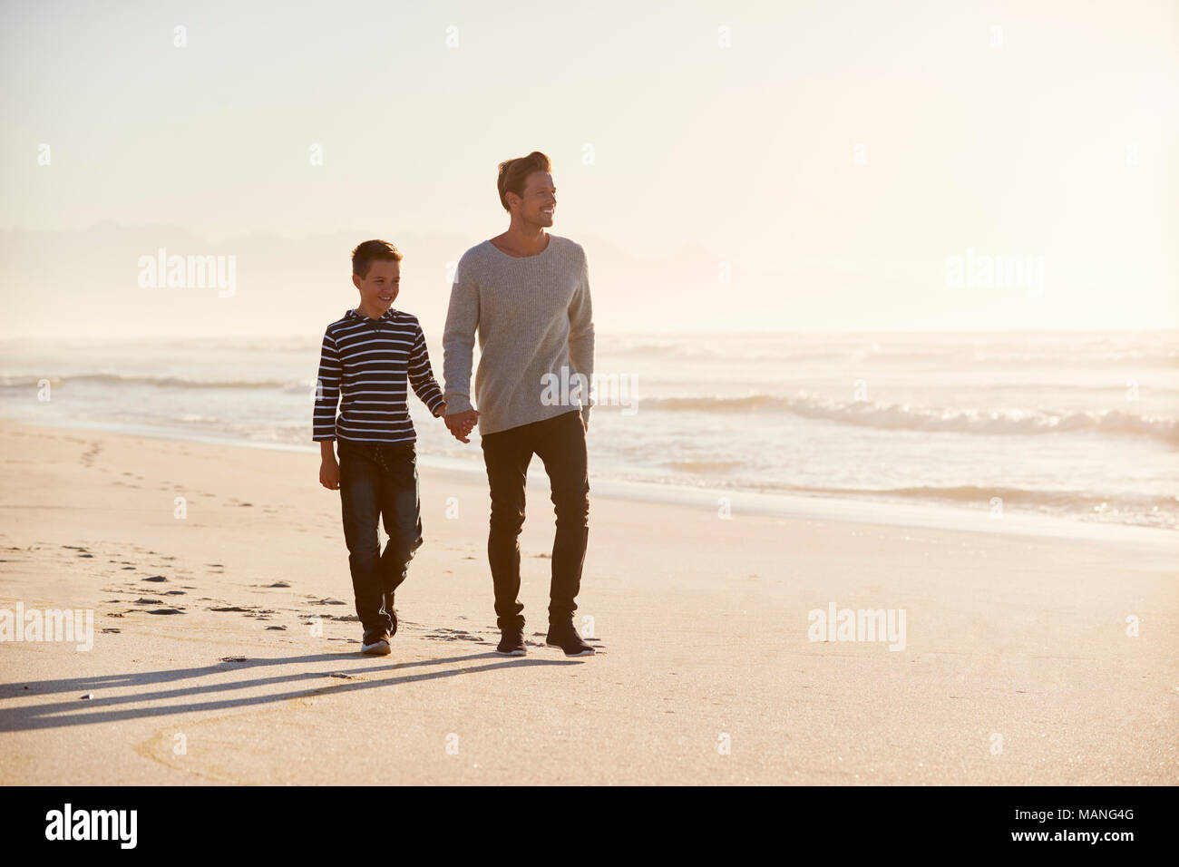 Father And Son Walking Along Winter Beach Hand In Hand - Stock Image