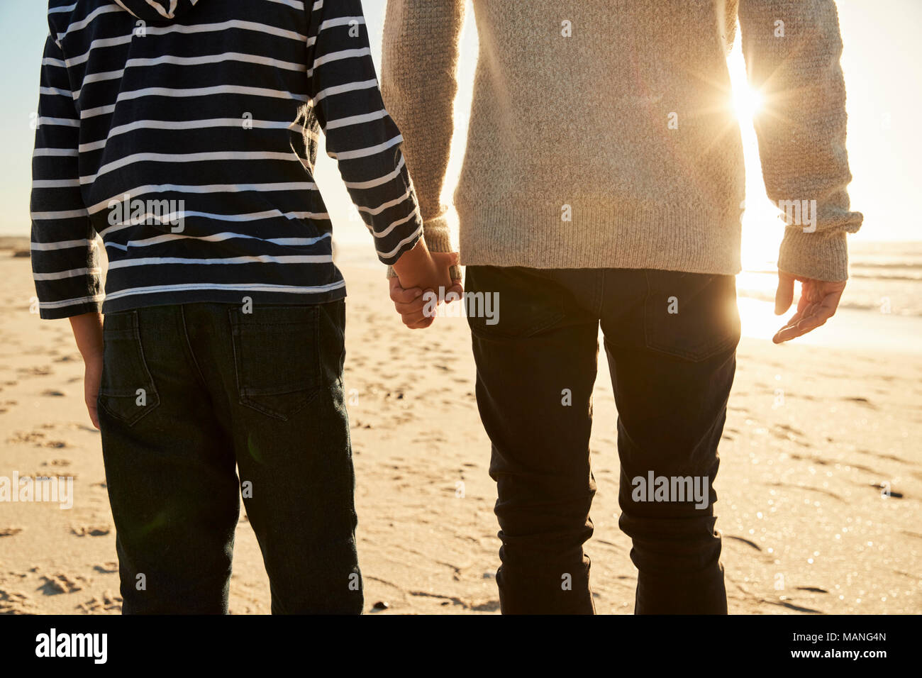 Detail Of Father And Son Walking Along Winter Beach Hand In Hand - Stock Image