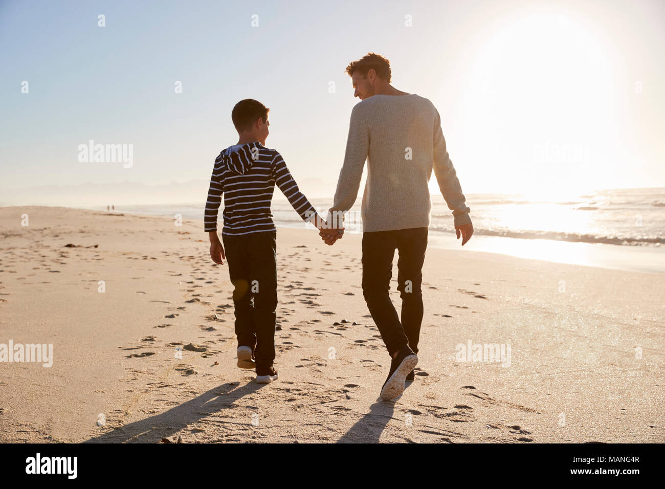 Rear View Of Father And Son Walking On Winter Beach Hand In Hand - Stock Image