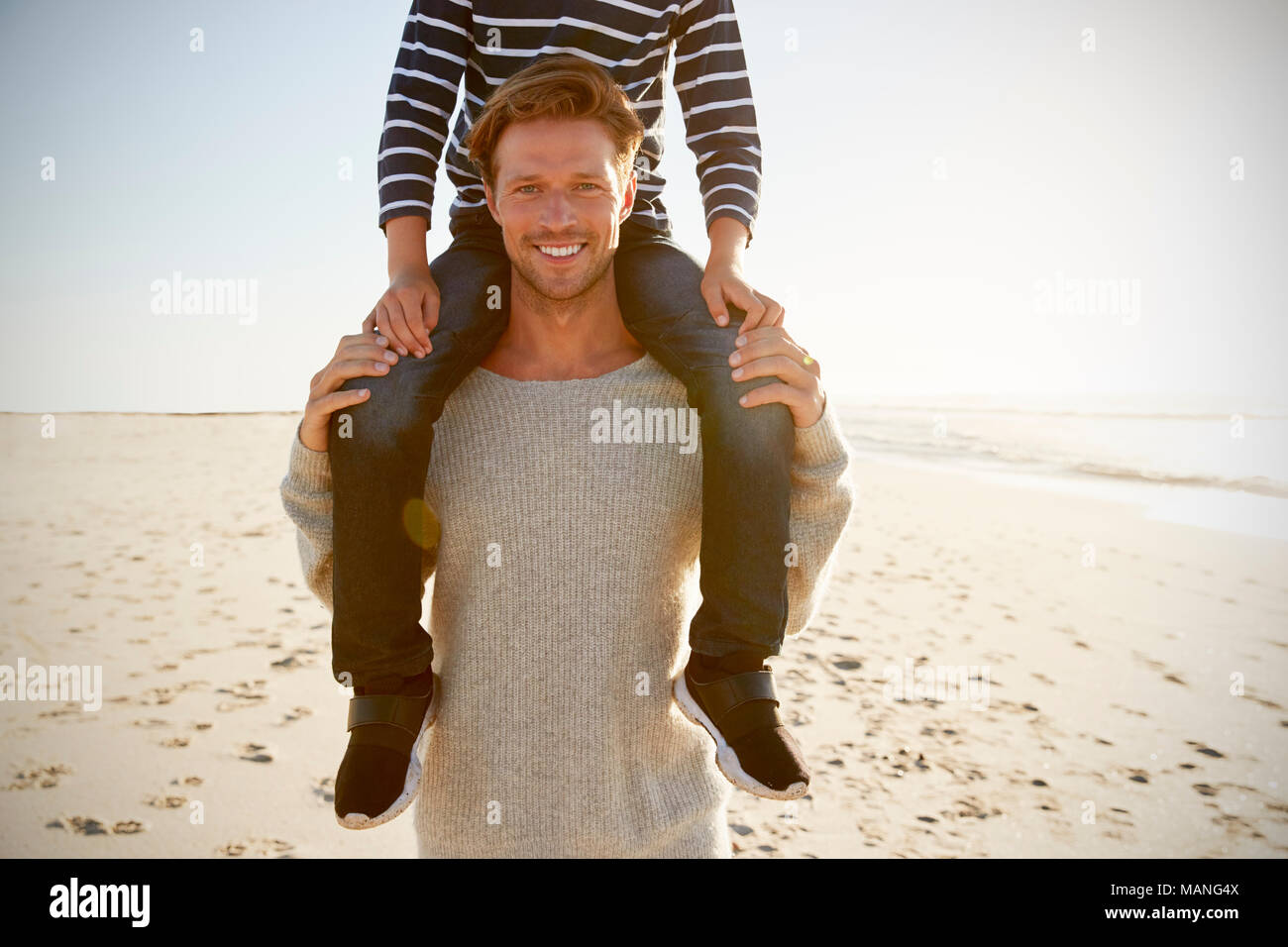 Detail Of Father Carrying Son On Shoulders On Winter Beach - Stock Image