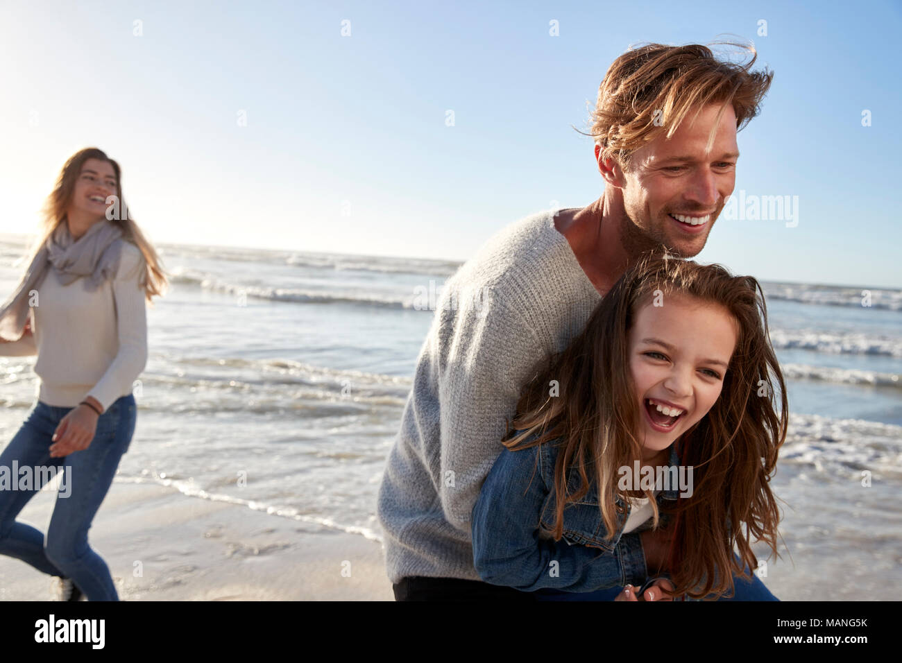 Parents With Daughter Having Fun On Winter Beach Together - Stock Image