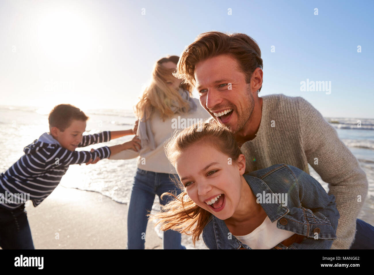Parents With Children Having Fun On Winter Beach Together - Stock Image