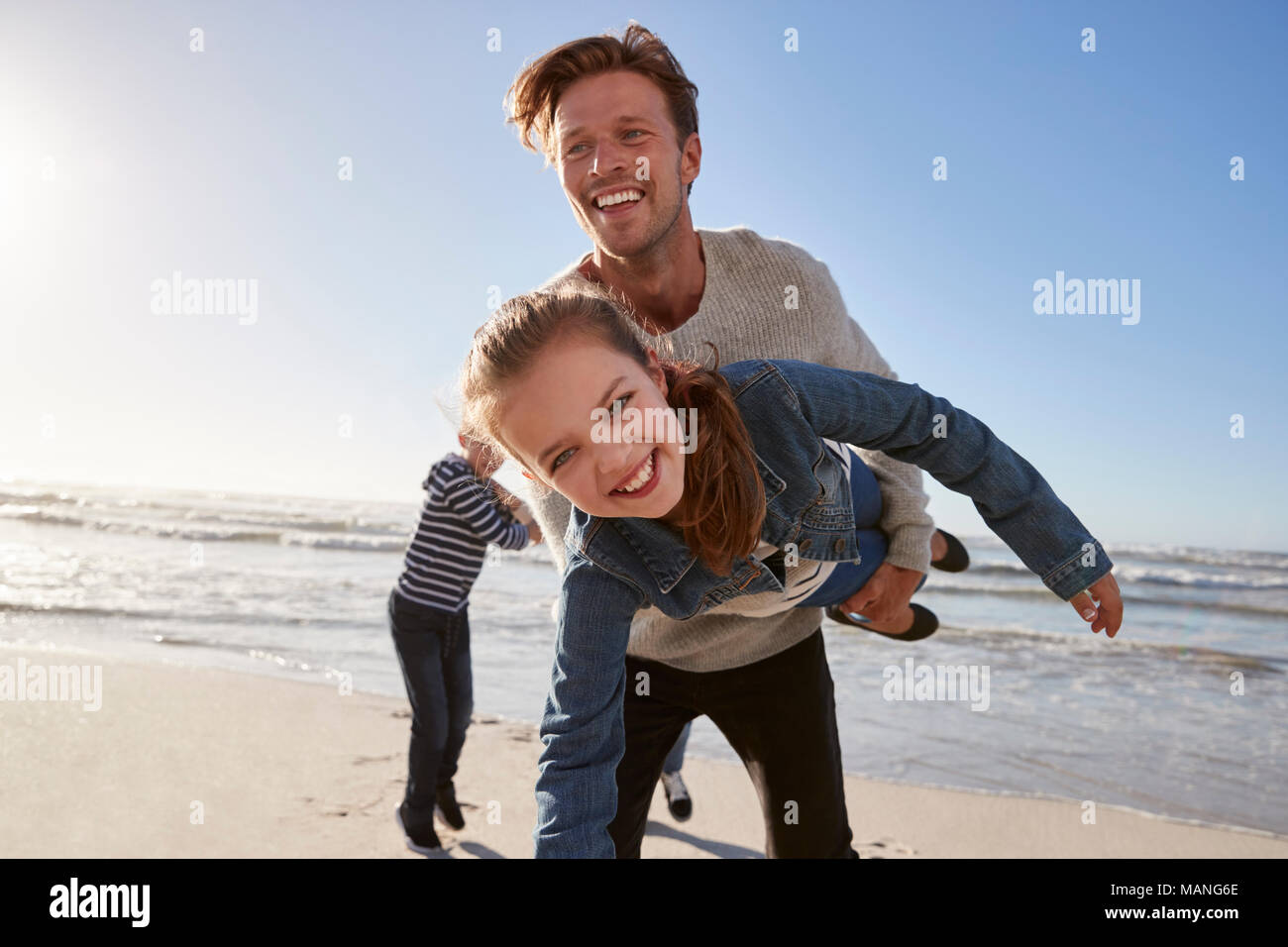 Father With Children Having Fun On Winter Beach Together - Stock Image