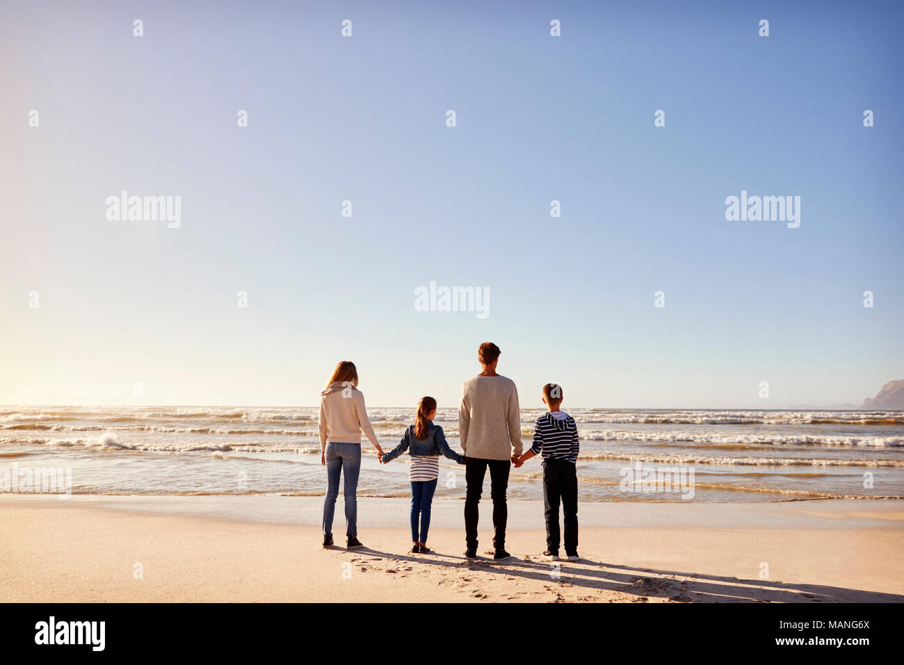 Rear View Of Family On Winter Beach Holding Hands Looking At Sea Stock Photo