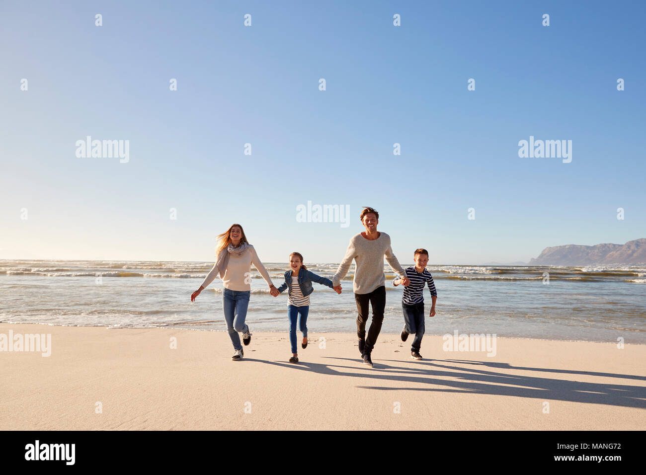 Family On Winter Beach Holding Hands And Running Towards Camera - Stock Image