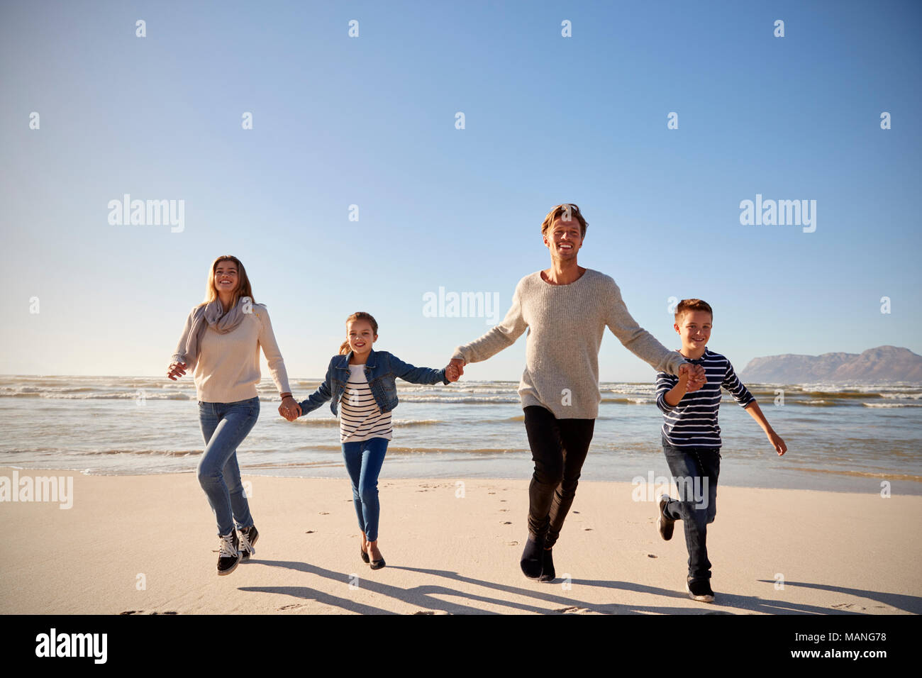 Family On Winter Beach Holding Hands And Running Towards Camera Stock Photo