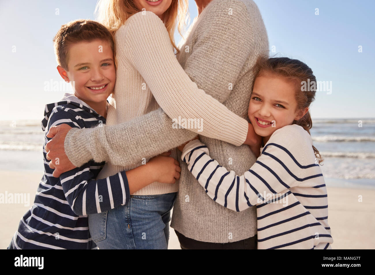 Close Up Of Children Hugging Parents On Winter Beach - Stock Image
