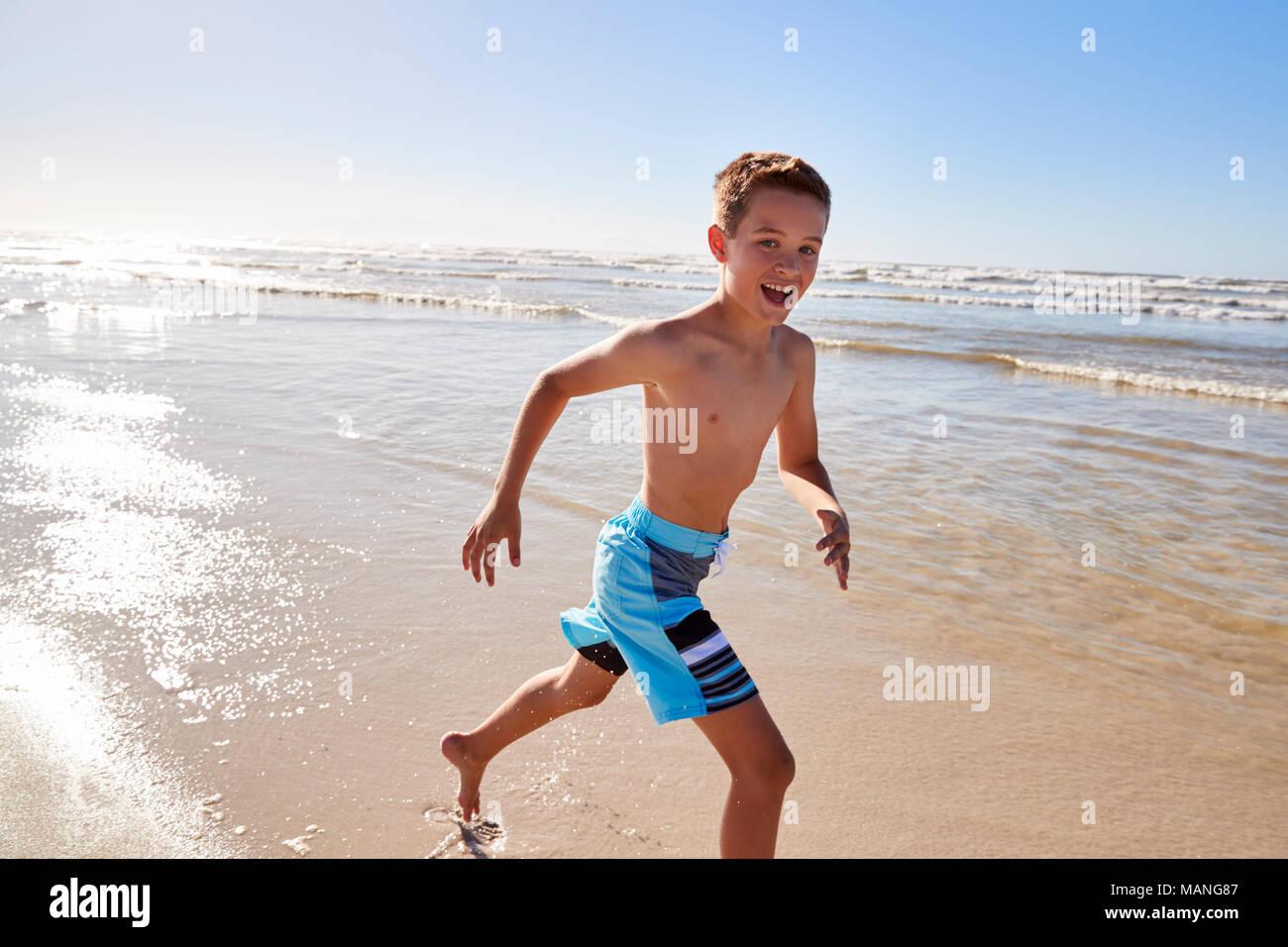 Portrait Of Boy Running Through Waves On Summer Vacation Stock Photo