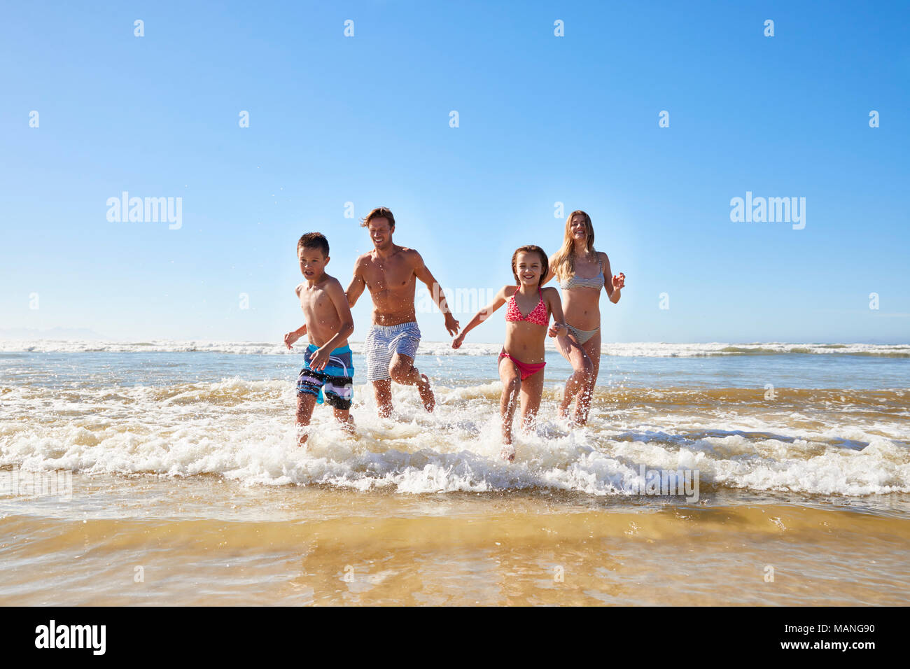 Family On Summer Beach Vacation Run Out Of Sea Towards Camera - Stock Image