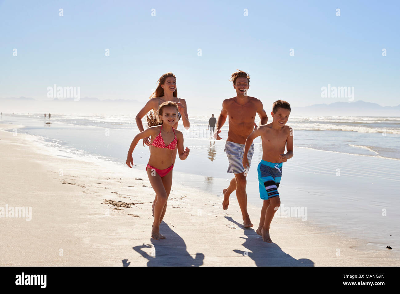 Family On Summer Vacation Running Along Beach Together - Stock Image