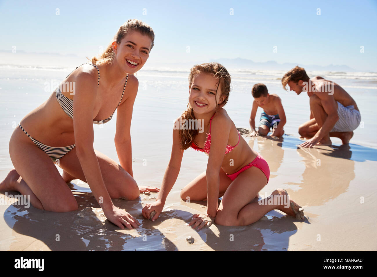 Family On Summer Vacation Playing On Beach Together - Stock Image