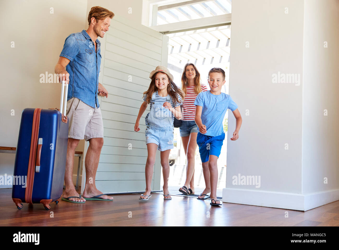 Family Arriving At Summer Vacation Rental - Stock Image
