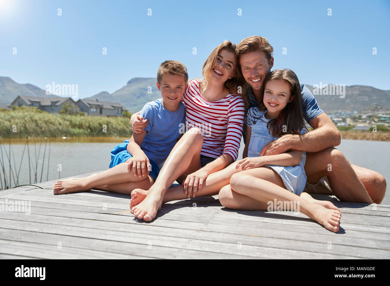Portrait Of Smiling Family Sitting On Wooden Jetty By Lake - Stock Image