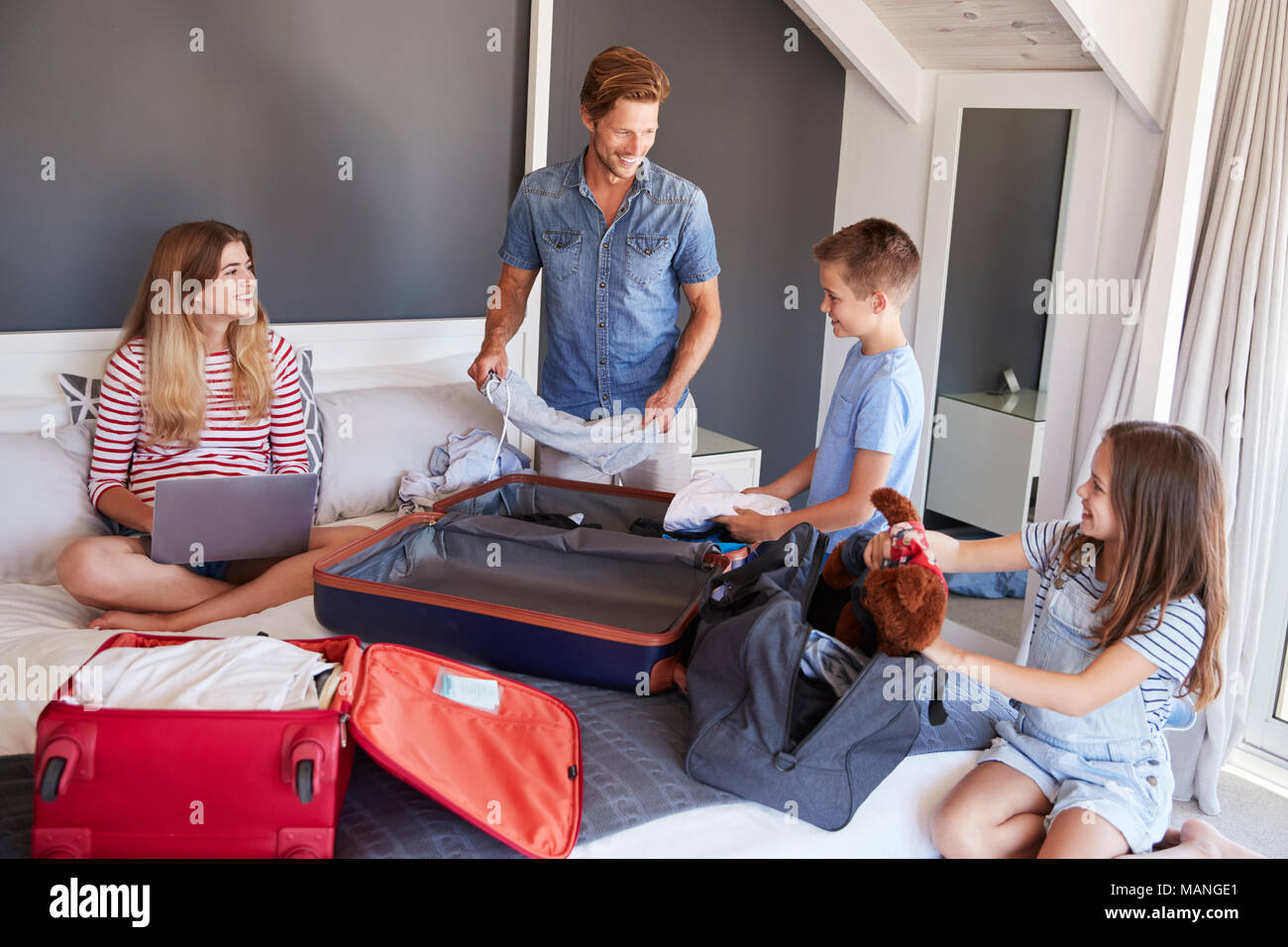 Family In Bedroom Pack Suitcases For Vacation And Use Laptop - Stock Image