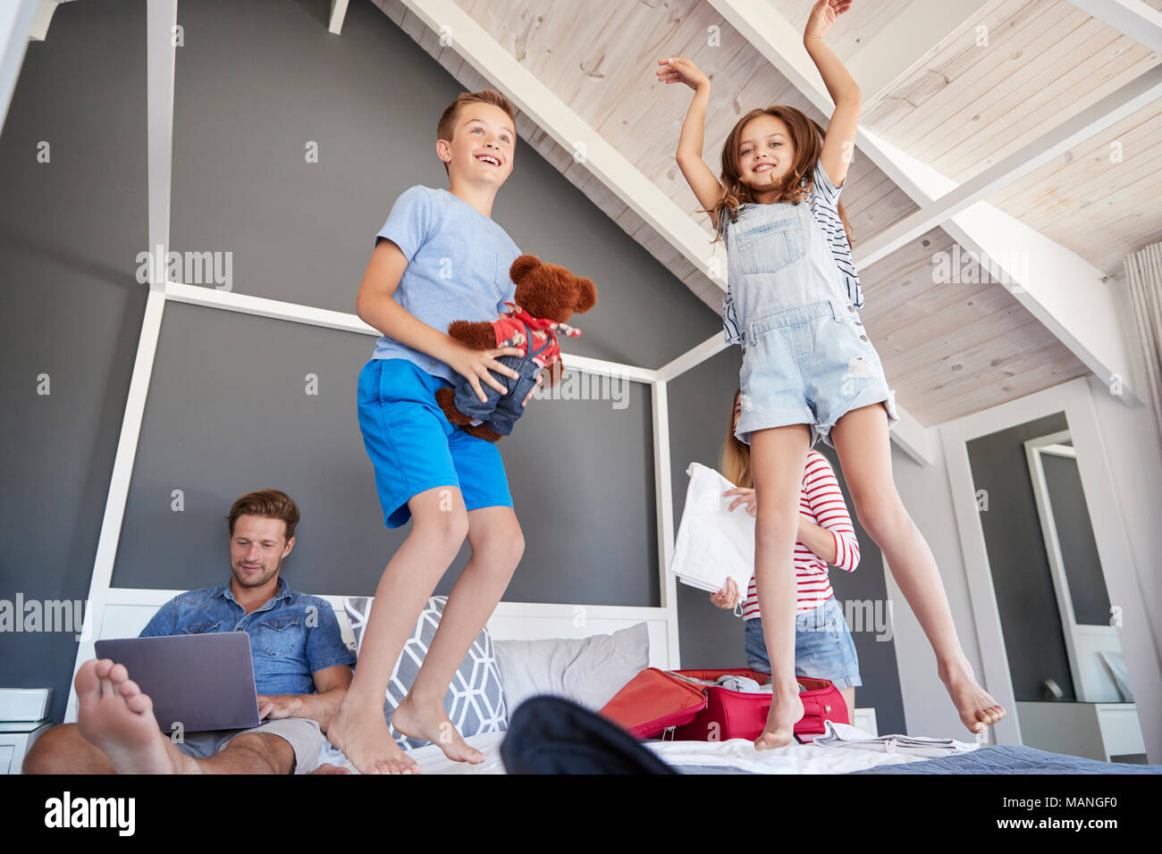Excited Children Jump On Bed As Parents Pack For Vacation - Stock Image