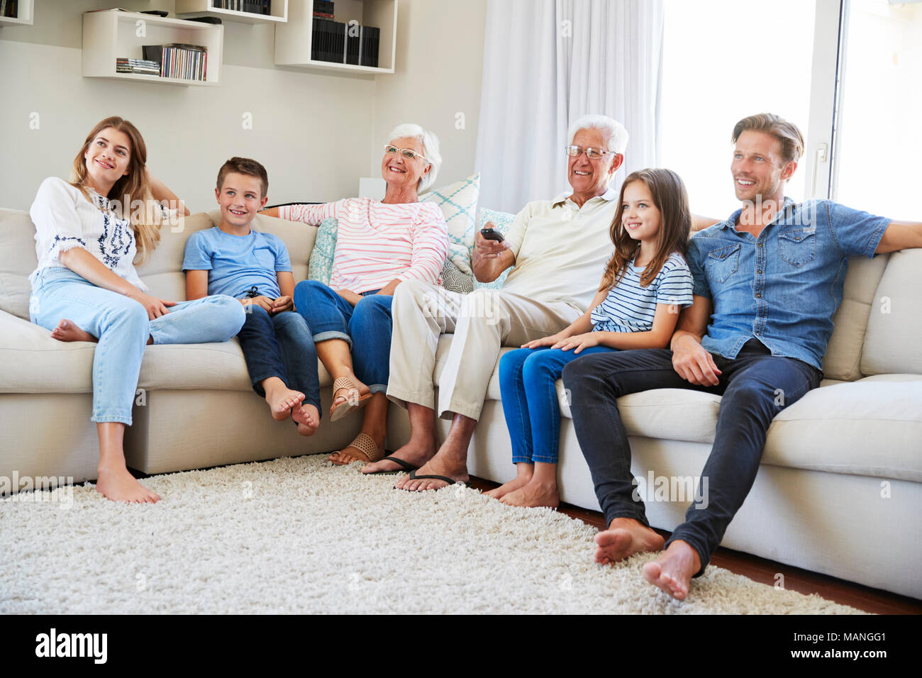 Multi Generation Family Sitting On Sofa At Home Watching TV - Stock Image
