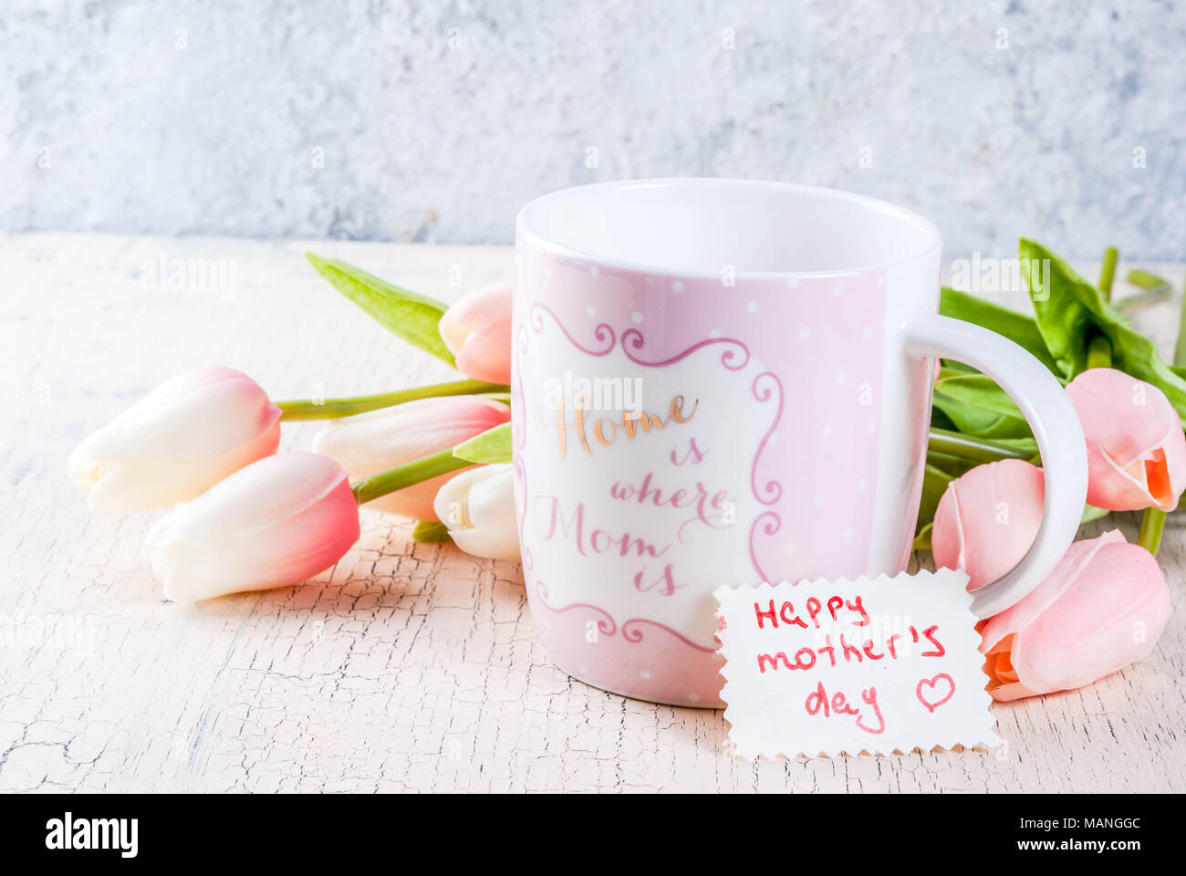 Mothers day concept greeting card background flowers tulips on a mothers day concept greeting card background flowers tulips on a light concrete table mug with inscription home is where the mom is greeting no m4hsunfo