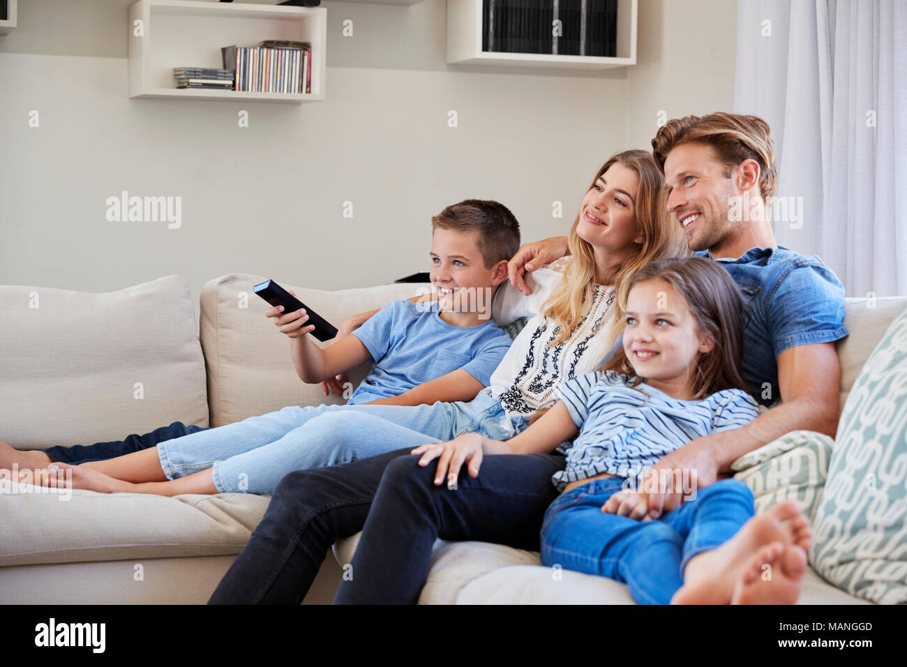 Family Sitting On Sofa At Home Watching TV Together - Stock Image